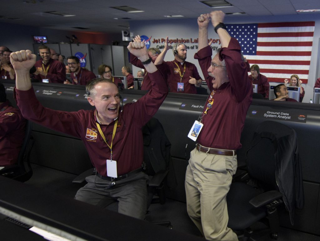 Mars InSight team members Kris Bruvold, left, and Sandy Krasner rejoice Monday inside the Mission Support Area at NASA's Jet Propulsion Laboratory in Pasadena, California, after receiving confirmation that the Mars InSight lander successfully touched down on the surface of Mars.