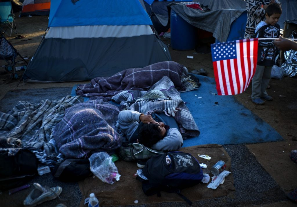 A migrant holding a U.S. flag, right, speaks with others waking up at the Benito Juarez Sports Center that's serving as a temporary shelter in Tijuana, Mexico, early Monday. The mayor of Tijuana has declared a humanitarian crisis in his border city and says that he has asked the United Nations for aid to deal with thousands of Central American migrants who have arrived in the city.