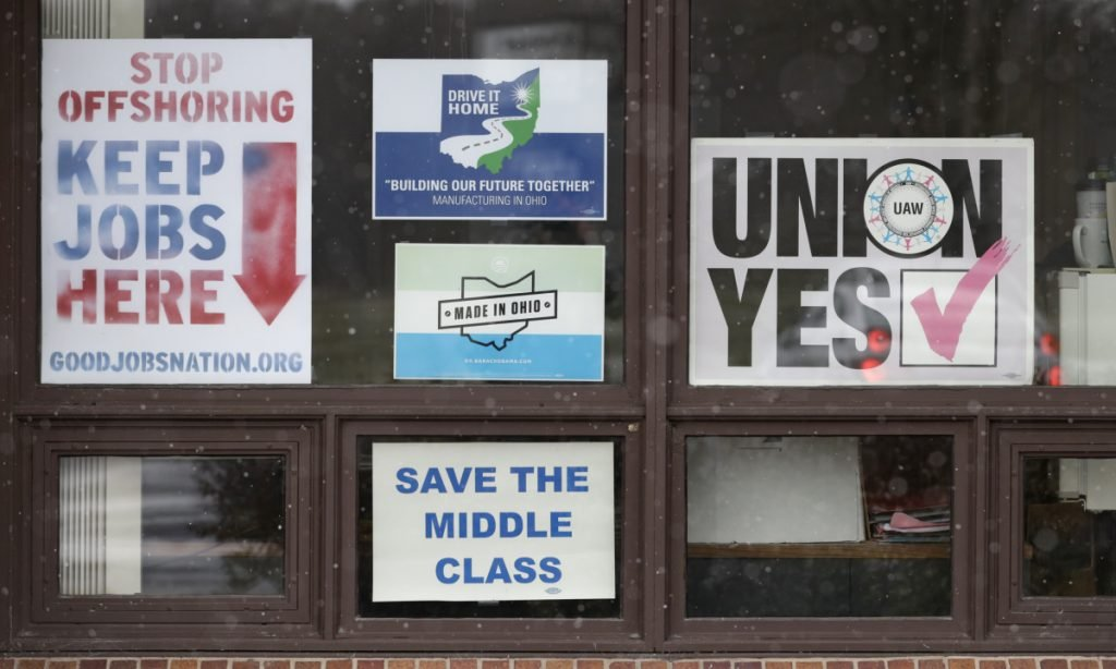 Signs hang in windows at the UAW Local 1112 union hall Tuesday in Lordstown, Ohio. Even though unemployment is low, the economy is growing and U.S. auto sales are near historic highs, GM is cutting thousands of jobs in a major restructuring aimed at generating cash to spend on innovation. GM put five plants up for possible closure, including the plant in Lordstown.