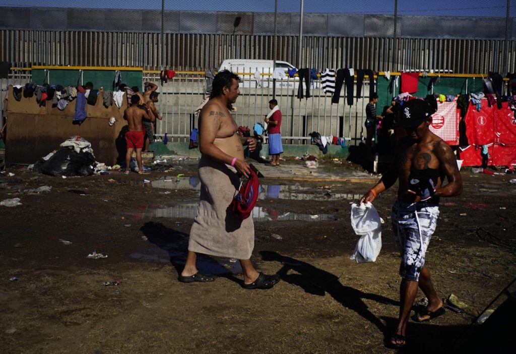 People who are part of the migrant caravan bathe at the Benito Juarez Sports Center, which is serving as a temporary shelter, in Tijuana, Mexico, on Tuesday.