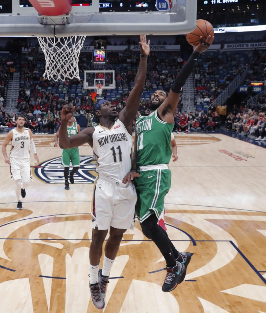 Boston Celtics guard Kyrie Irving, front right, goes to the basket against New Orleans Pelicans guard Jrue Holiday, front left, in the first half of an NBA basketball game in New Orleans, Monday, Nov. 26, 2018. ()
