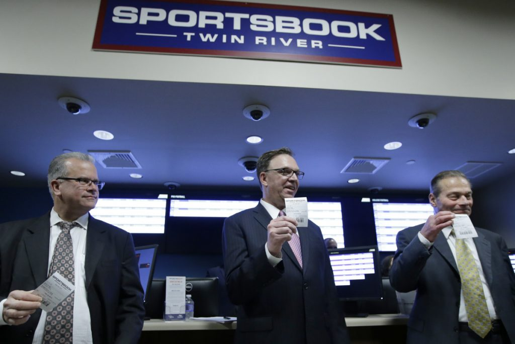 Rhode Island House Speaker Nicholas Mattiello, Twin River executive John Taylor and Rhode Island Senate President Dominick Ruggerio, right, display tickets after placing the first legal sports bets Monday at Twin River Casino Hotel, in Lincoln, R.I.