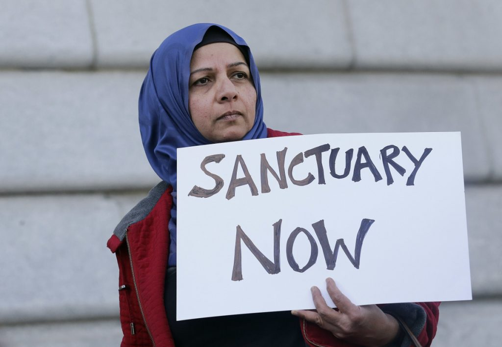 "A woman holds a sign at a rally outside of City Hall in San Francisco in 2017. The Trump administration can't withhold over $29 million from six states and New York City in a clash over their immigration policies as ""sanctuary"" jurisdictions, a federal judge said Friday."