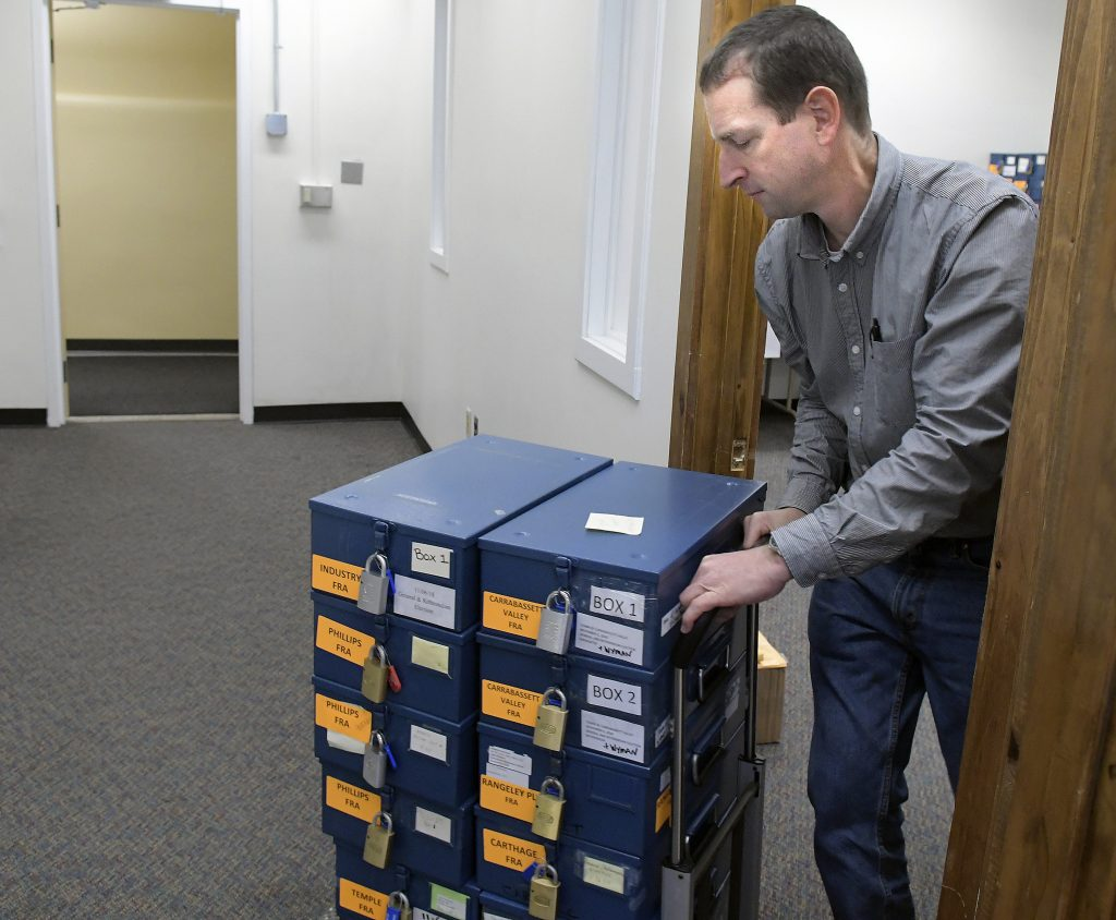 Secretary of State's Office employee Tom Bull moves ballot boxes on Monday during a tabulation of votes for Maine's 2nd Congressional District race between Jared Golden and Rep. Bruce Poliquin in Augusta.