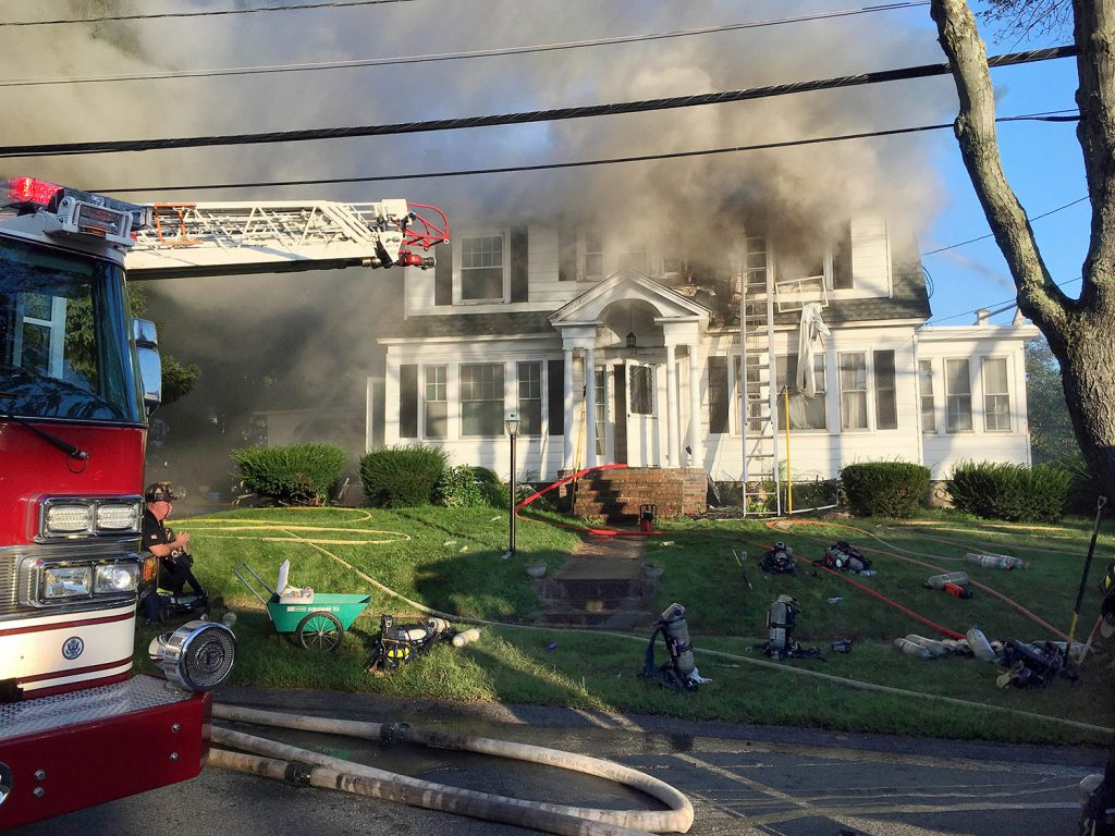 Firefighters battle a house fire on Thursday on Herrick Road in North Andover, Mass., one of multiple emergency crews responding to a series of gas explosions and fires triggered by a problem with a gas line that feeds homes in several communities north of Boston.