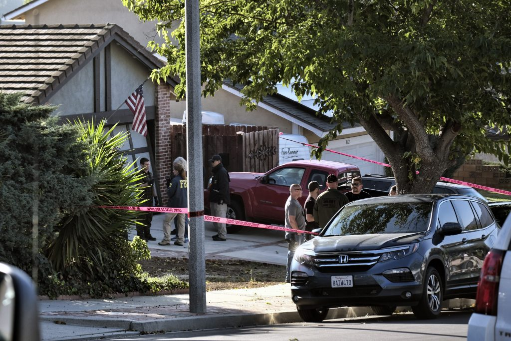 Ventura County Sheriff's deputies and FBI investigators stand outside the house of shooting suspect David Ian Long in Newbury Park, Calif., on Thursday,. Authorities said the former Marine opened fire at a country music bar in Southern California on Wednesday night, killing 12.