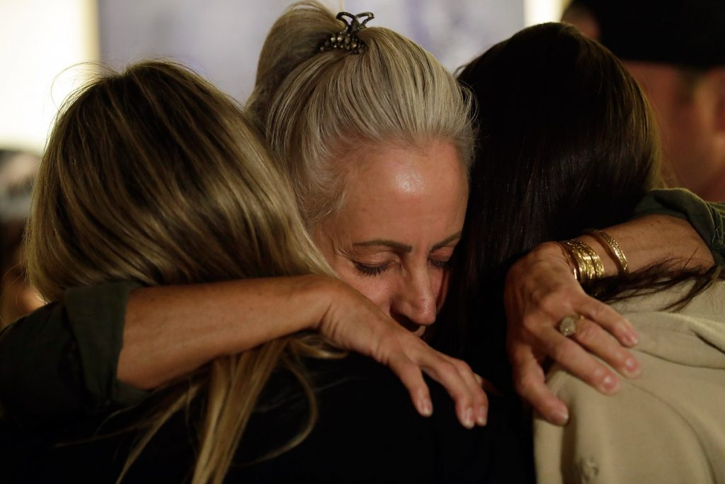 Mourners embrace during a vigil to remember victims of a mass shooting, on Thursday in Thousand Oaks, Calif. Terrified patrons hurled barstools through windows to escape or threw their bodies protectively on top of friends as a Marine combat veteran killed multiple people at a country music bar in an attack that added Thousand Oaks to the tragic roster of American cities traumatized by mass shootings.