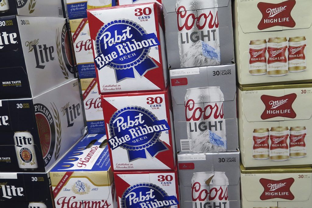 In this Nov. 8, 2018, file photo, cases of Pabst Blue Ribbon and Coors Light are stacked next to each other in a Milwaukee liquor store. MillerCoors and Pabst Brewing Co. settled a lawsuit Wednesday, Nov. 28, in which the hipster's brand of choice claimed the bigger brewer lied about its ability to continue brewing Pabst's beers to put that company out of business.