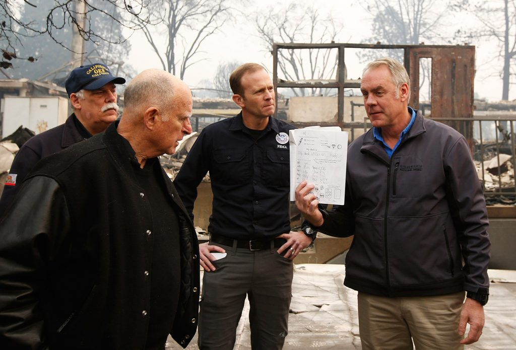 California Gov. Jerry Brown looks at a student's work book, held by Interior Secretary Ryan Zinke, that was found in the fire-ravaged Paradise Elementary School on Wednesday. The school is among the thousands of homes and businesses destroyed when a wildfire burned through Paradise last week.