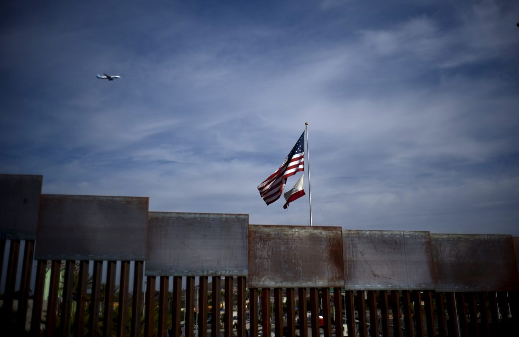U.S. and California state flags fly behind the border wall, seen from Tijuana, Mexico, Monday, Nov. 19, 2018. Tensions have built as nearly 3,000 migrants from a caravan poured into Tijuana in recent days after more than a month on the road — and with many more months likely ahead of them while they seek asylum in the U.S.