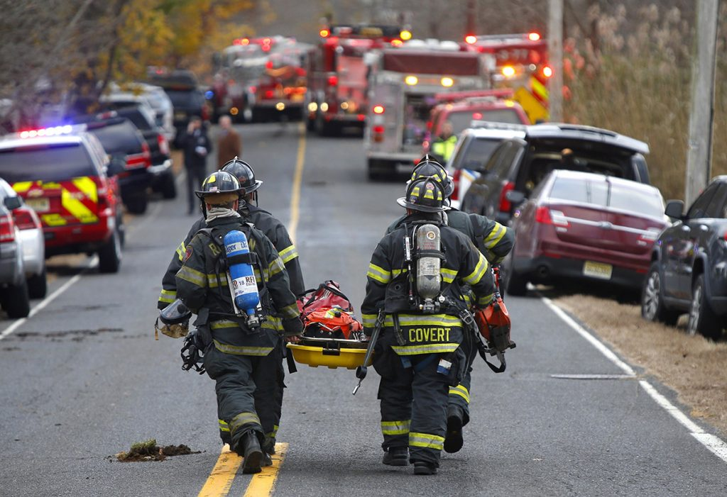 Firefighters carry a stretcher to the scene of a fatal fire Tuesday in Colts Neck, N.J.