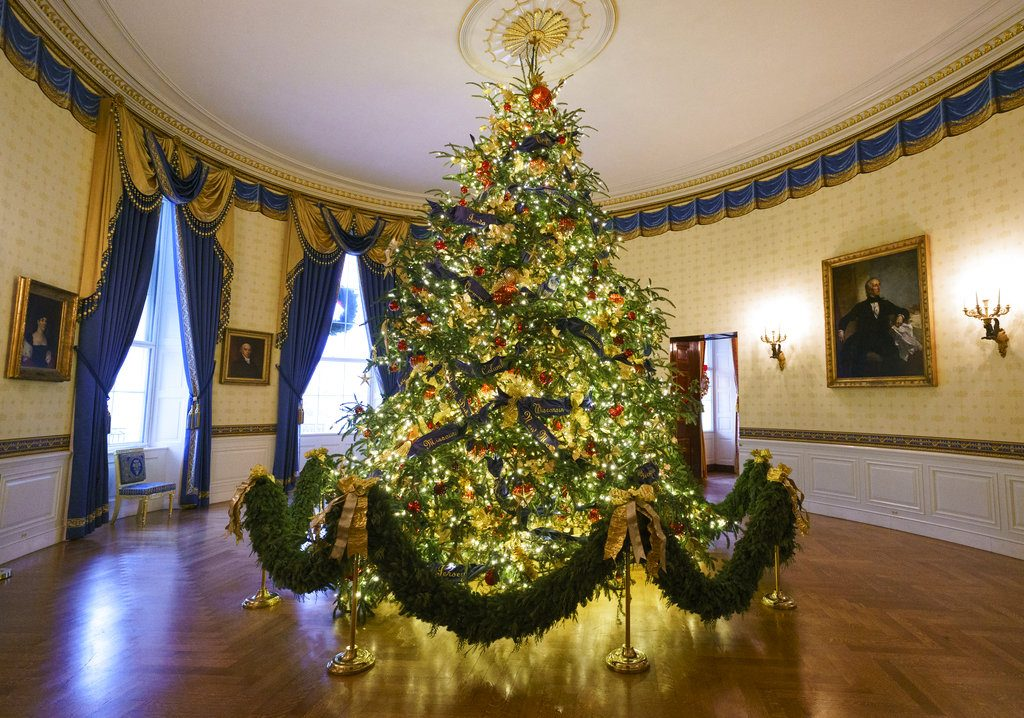 The official White House Christmas tree is seen in the Blue Room during the Christmas press preview at the White House in Washington, Monday. The tree measures 18 feet tall and is dressed in over 500 feet of blue velvet ribbon embroidered in gold with each State and territory.