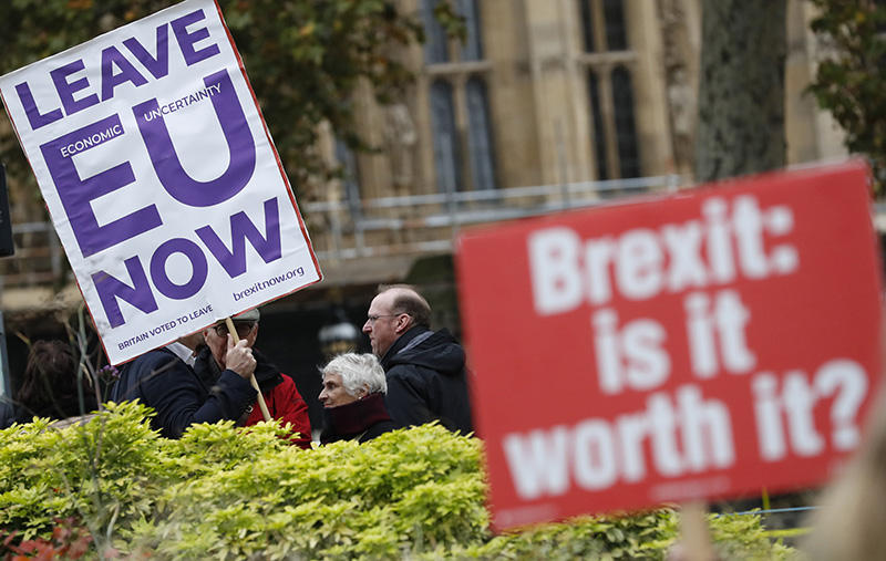 Pro and anti Brexit protesters hold placards as they vie for media attention near Parliament in London on Friday.