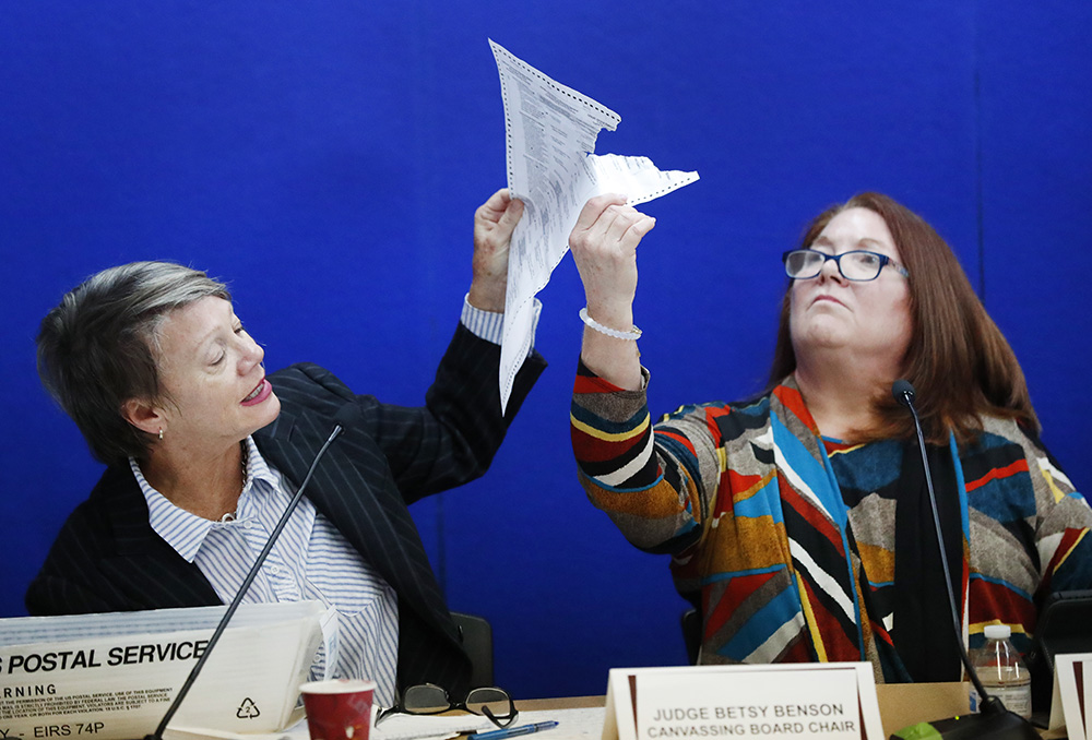 Canvassing Board chair Judge Betsy Benson, left, and board member Judge Deborah Carpenter-Toye, right, show political lawyers one of the ballots that was damaged during the recount that will need to be duplicated and then recounted, at the Broward County Supervisor of Elections office on Wednesday.