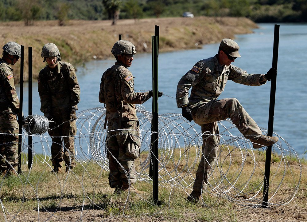 Members of the U.S. military install multiple tiers of concertina wire along the banks of the Rio Grande near the Juarez-Lincoln Bridge at the U.S.-Mexico border in Texas on Friday.