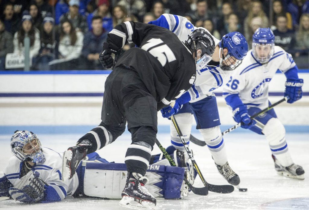 Colby College goalie Andrew Tucci (1) lies flat on his stomach as Bowdoin College's Thomas Dunleavy (15) looks to score with Colby's Austen Halpin (6) defending during a game at Alfond Rink in Waterville earlier this season.