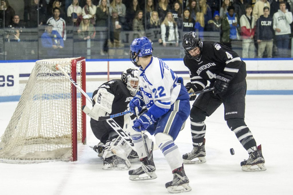 Colby College's Nick O'Connor (22) looks to score on Bowdoin College goalie Erik Wurman (35) as Bowdoin's 	Collin Van der Veen (4) tries to defend  at Colby College in Waterville on Saturday.