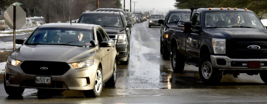 "As students and staff leave Skowhegan Area High School on Monday, state police Det. Bryant Jacques, in unmarked cruiser at left, also leaves the school grounds following a posted threat to the school. ""I did some drive-through passes at the school today to let students know we (law enforcement) are present,"" Jacques said."