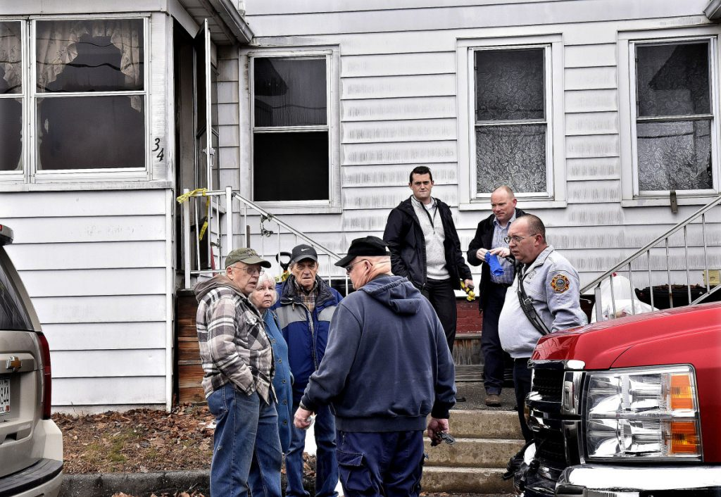 Senior Fire Investigator Ken MacMaster, center, of the state Fire Marshal's Office, speaks with duplex owner Roland Hallee, left, outside his duplex at 34 Green St. in Waterville on Monday. Other investigators and Waterville Fire Capt. John Gromek, right, were at the scene to determine the cause of the fire that occurred late Saturday evening.