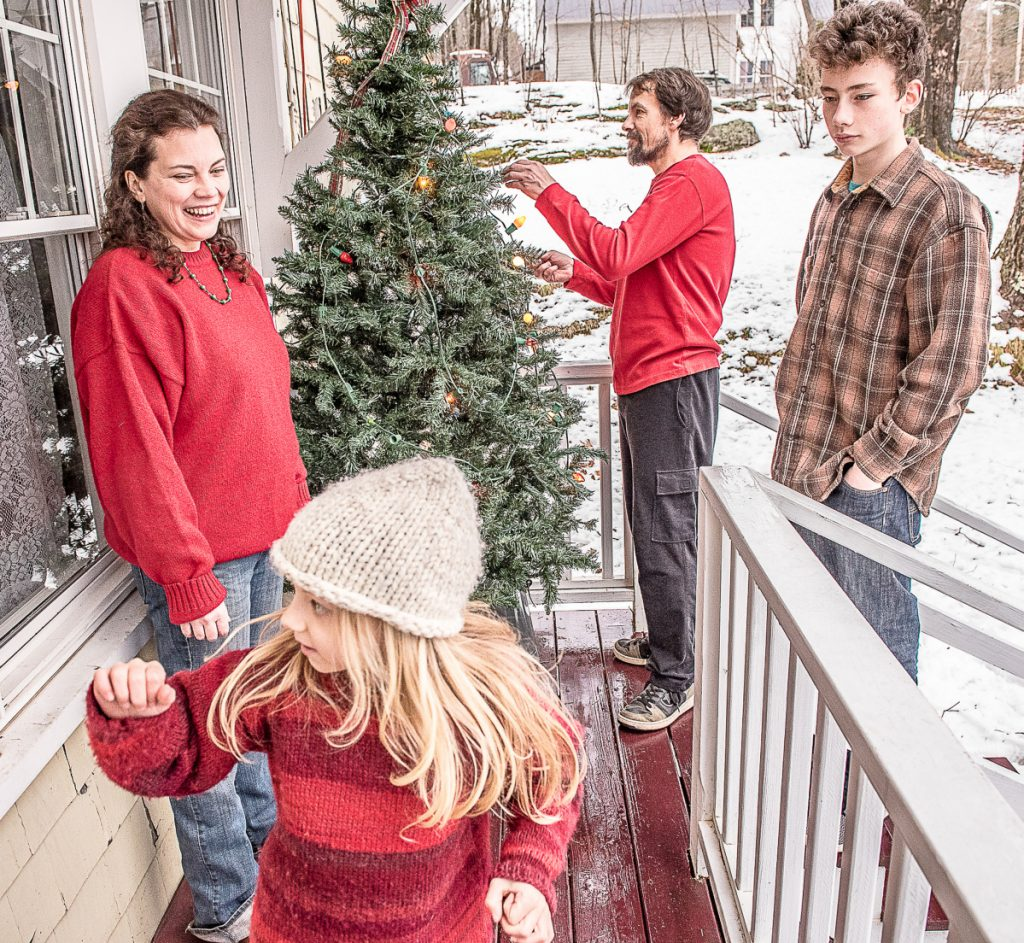 D'Arcy Ames and her partner, Gary Couture, hang lights on their outdoor Christmas tree at their Auburn home with the help of children Vivian and Calvin. The family is facing severe financial hardship and risks losing the house as Couture recovers from Lyme disease.