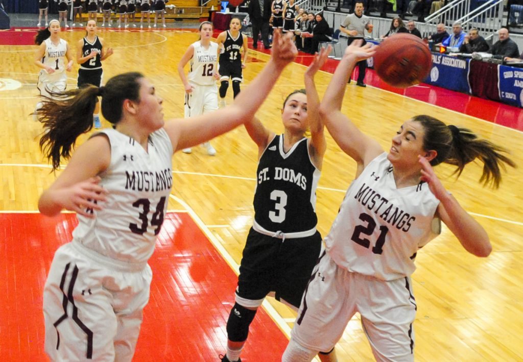 Monmouth center Destiny Clough, left, and guard Abby Ferland, right go for a rebound in front of St. Dom's guard Raleigh Stebbins during a Class C South game last season at the Augusta Civic Center.