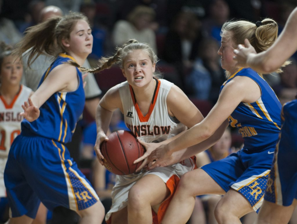 Seeking an opening: Winslow's Silver Clukey splits Lake Region defenders Rachel Shanks, left, and Shauna Hancock on her way to the basket during the Class B state championship game last season at the Cross Insurance Center in Bangor.