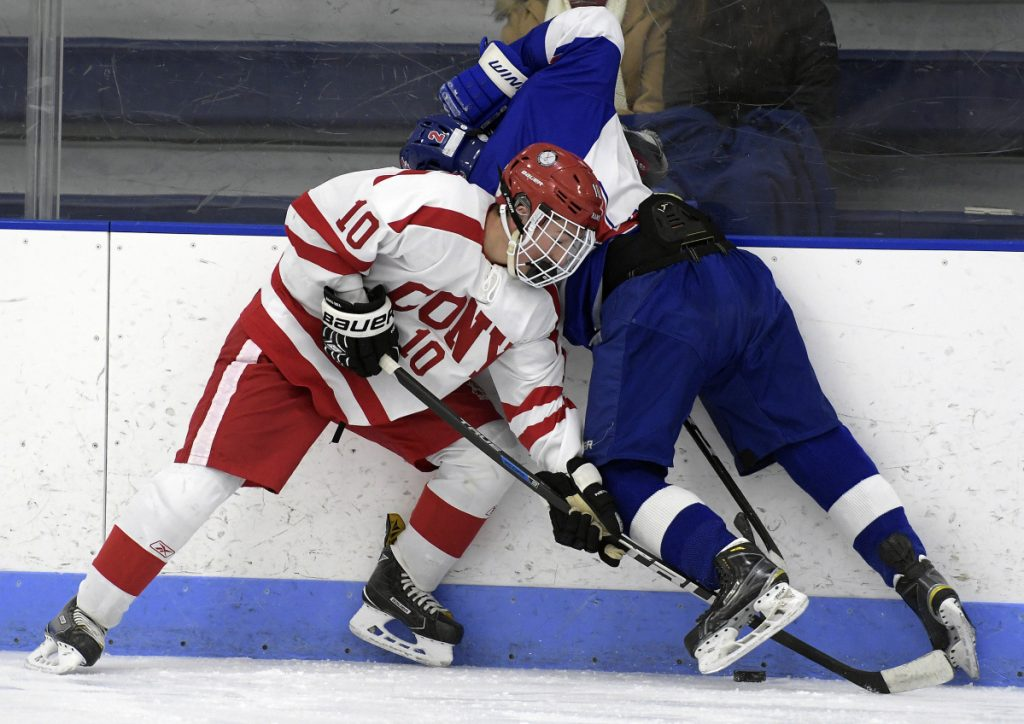 Cony's Michael Boivin, left, reaches for the puck under Lisbon/Mt. Ararat/Morse defenseman Noah Magda during a Class A North game last season in Hallowell.