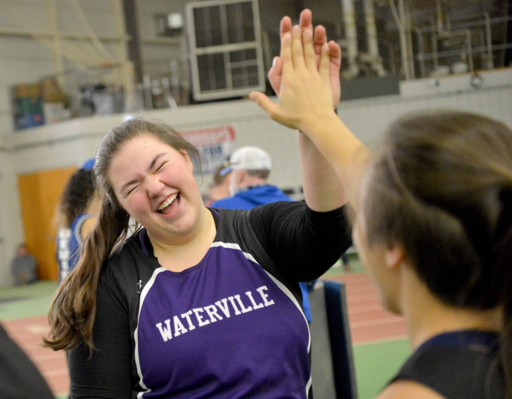 Waterville's Sarah Cox, center, highs-fives teammate Jennasea Hubbard after winning the shot put at the Kennebec Valley Athletic Conference track and field meet championships last Feb. 3 at Bowdoin College in Brunswick.