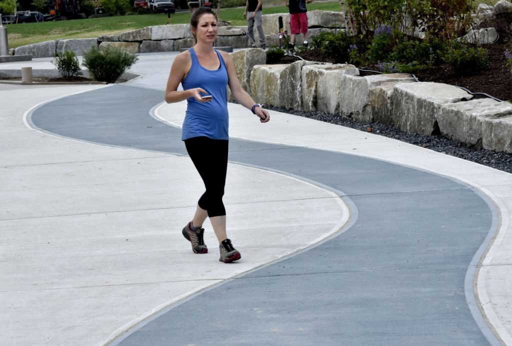 Katie Malone takes a leisurely walk Sept. 17 along the colorful paths at RiverWalk at Head of Falls in Waterville. The city of Waterville is to receive a $7.3 million grant to fund new traffic patterns and other infrastructure improvements downtown.