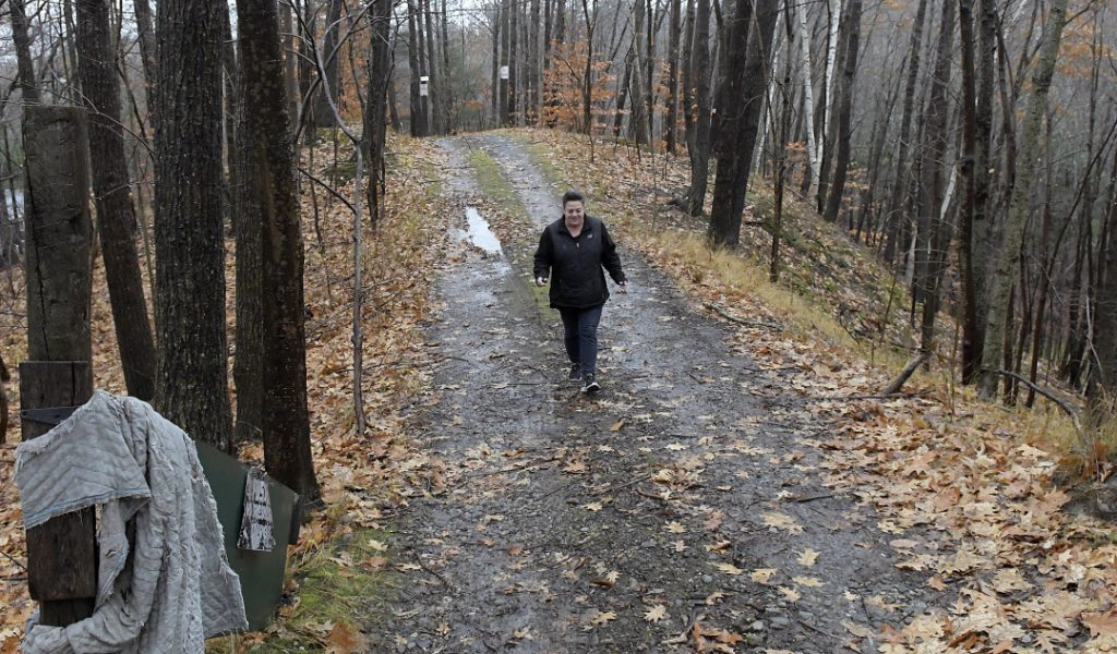 Monique Poulin walks down the road to her home, which faces Boothby Street, on Nov. 13 from pits at the Augusta Public Works facility.