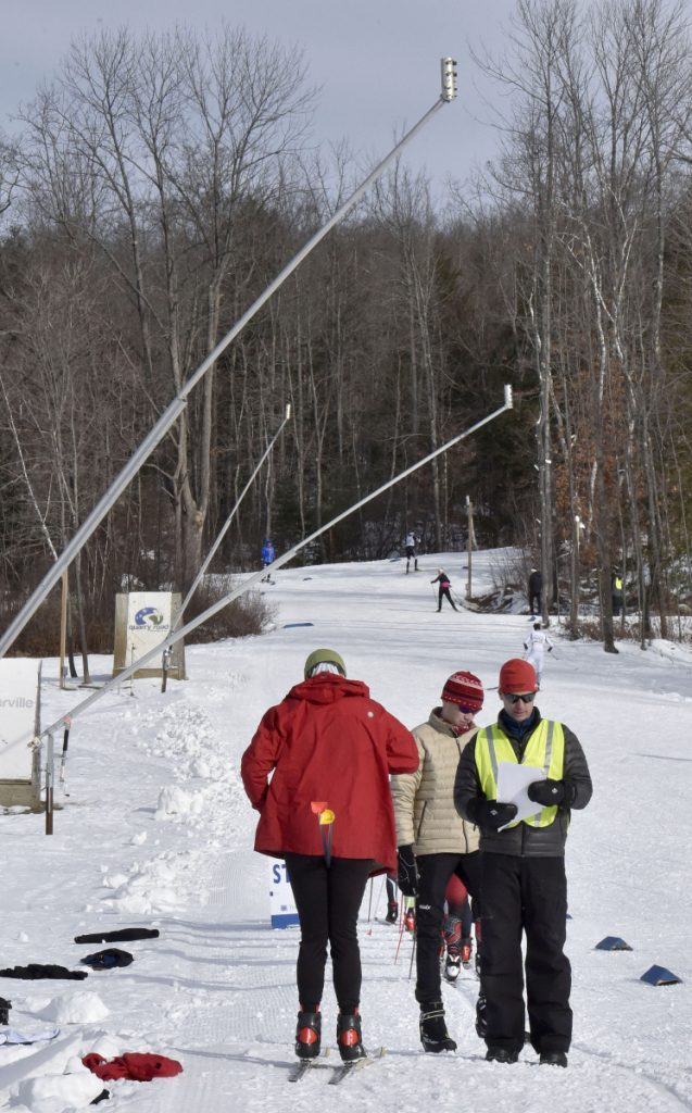 Under snowmaking guns along trails volunteer Kirk Ross, right, checks cross-country skiers assembled at the start for races during the Quarry Road Opener in Waterville on Sunday.