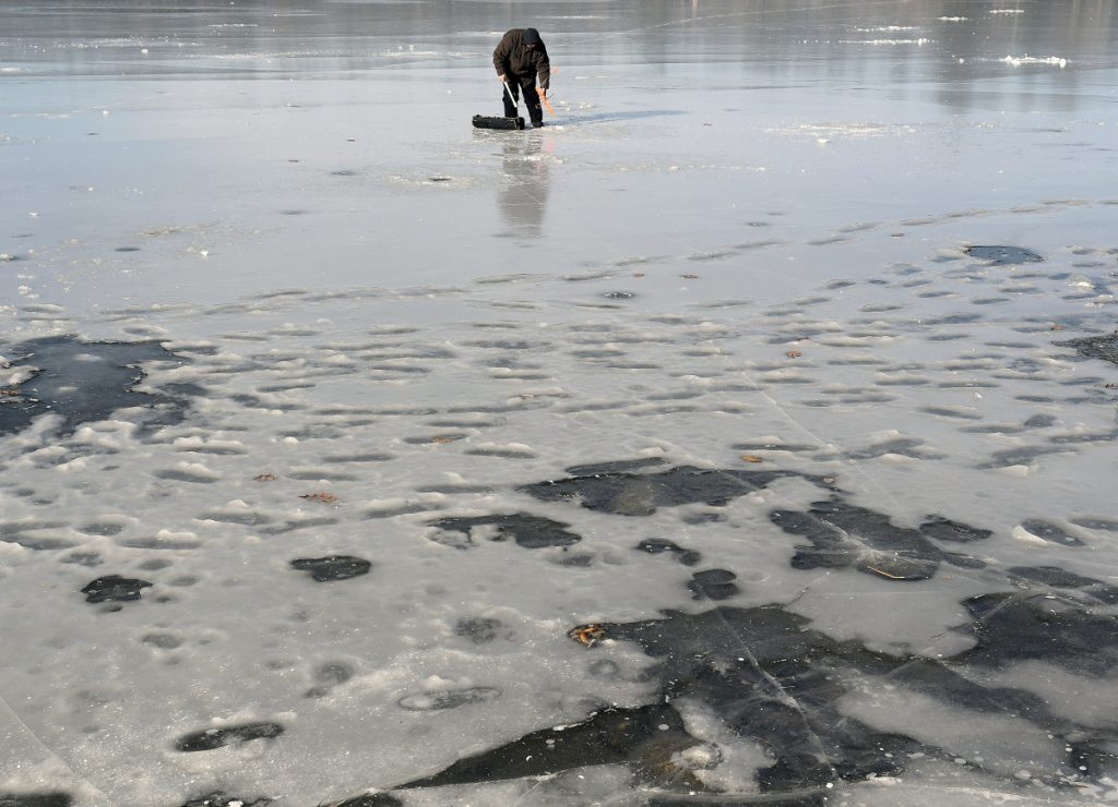 Rob Angelides, of Lewiston, collects a trap while ice fishing Sunday on Cochnewagon Pond in Monmouth. Cool temperatures have drawn anglers to the ice, which game wardens caution is still very thin on many bodies of water. Angelides said he caught a few small trout and cut through 6 inches of ice to put out his trap.