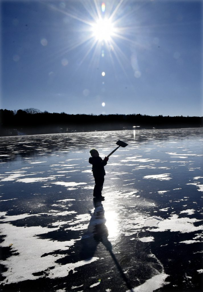 Landon Blaisdell swings an ice auger equal to his own height while he and his family fish on Messalonskee Lake in Oakland on a cold Monday. Landon's father reported the black ice was 4 inches thick.