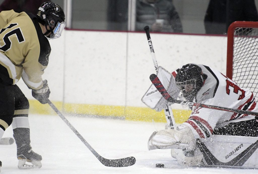 The Kings' Austin Taylor  can't move the puck past the Hawks' Will Hays during a game Monday in Readfield.