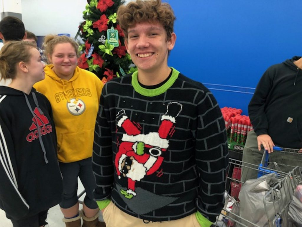Madison Area High School sophomore Christian Cabrera sports an ugly sweater of Santa Claus break dancing during a shopping spree Wednesday at the Skowhegan Walmart. Students from four area high schools were Christmas shopping for needy children with Jobs For Maine Graduates.