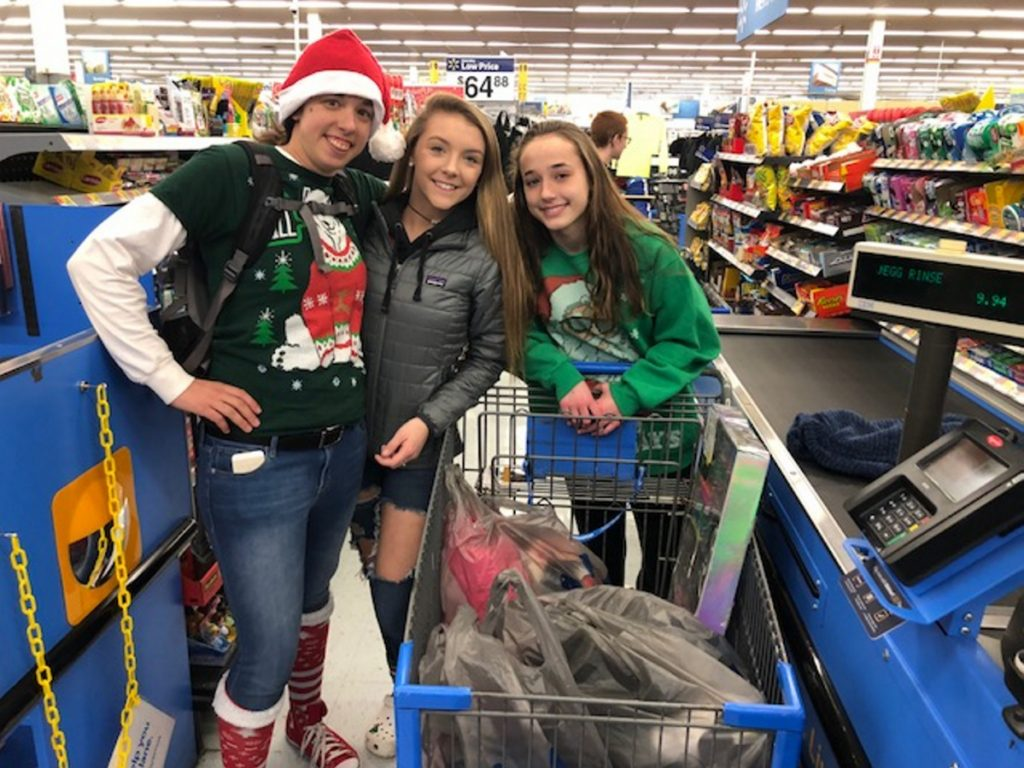 Steph Perkins, left, a Jobs for Maine Graduates specialist, and students Sierah Trask and Susanna Curtis check out after shopping Wednesday for Christmas gifts for needy children.