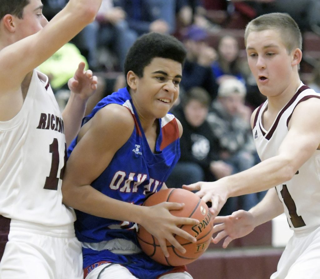 Richmond's Dakotah Gilpatric, left, and Ben Gardner play defense on Oak Hill's Ausborne Boston during a Mountain Valley Conference game Wednesday in Richmond.