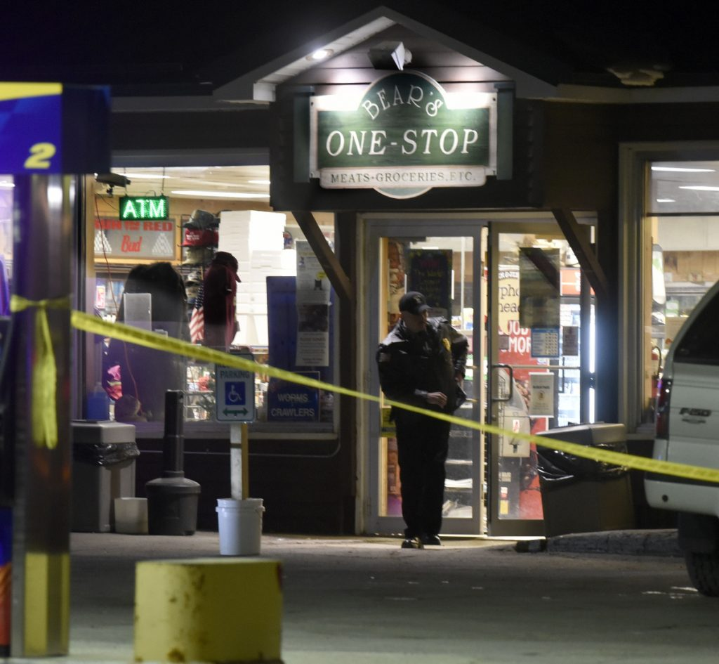 A police officer exits the Bear's One Stop store in Newport as other investigators inside speak with employees following a shooting early Wednesday evening.