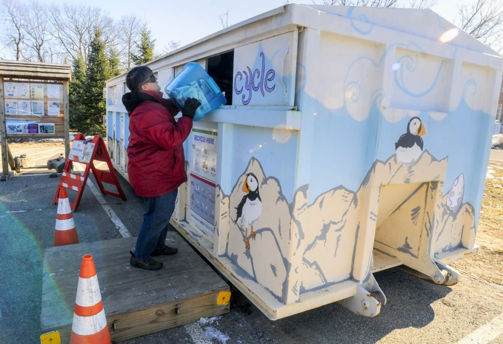 Jeanne Dumont dumps a bin of recyclables into an EcoMaine rolloff container Thursday at the Augusta police station.