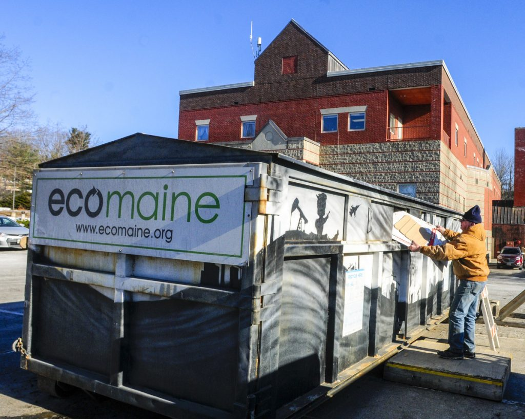 Les Mason puts cardboard into the Ecomaine recycling rolloff container Thursday at the Augusta police station.