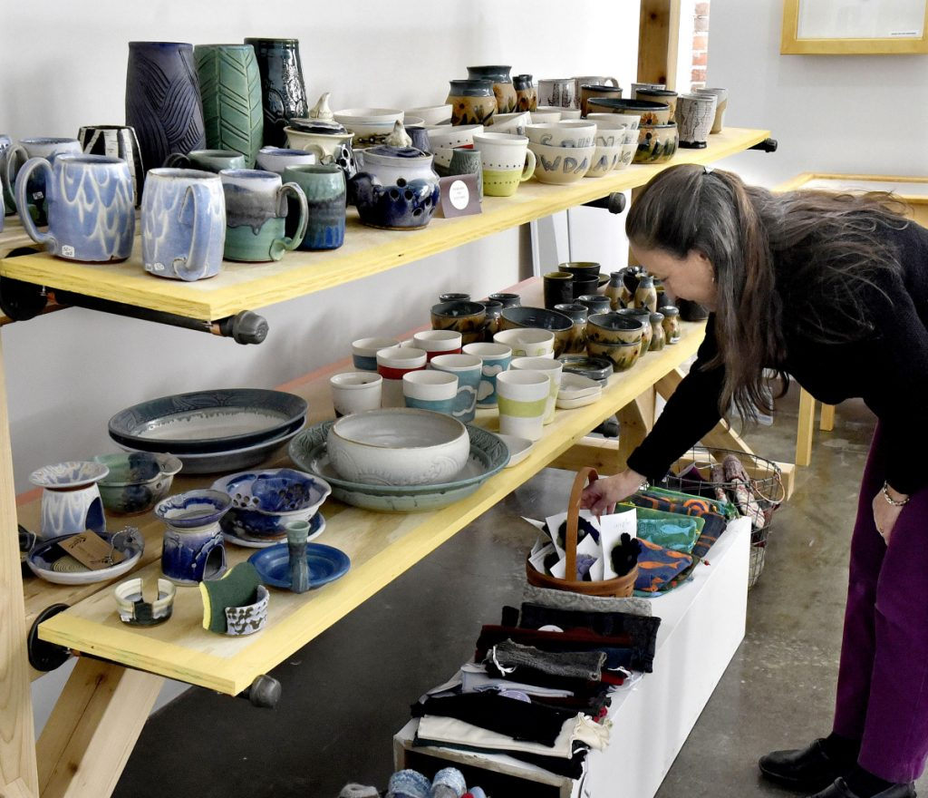 Customer Judy Ayer looks over pottery and knitted items at the holiday bazaar shop at Common Street Arts in the Hathaway Creative Center in Waterville on Thursday.