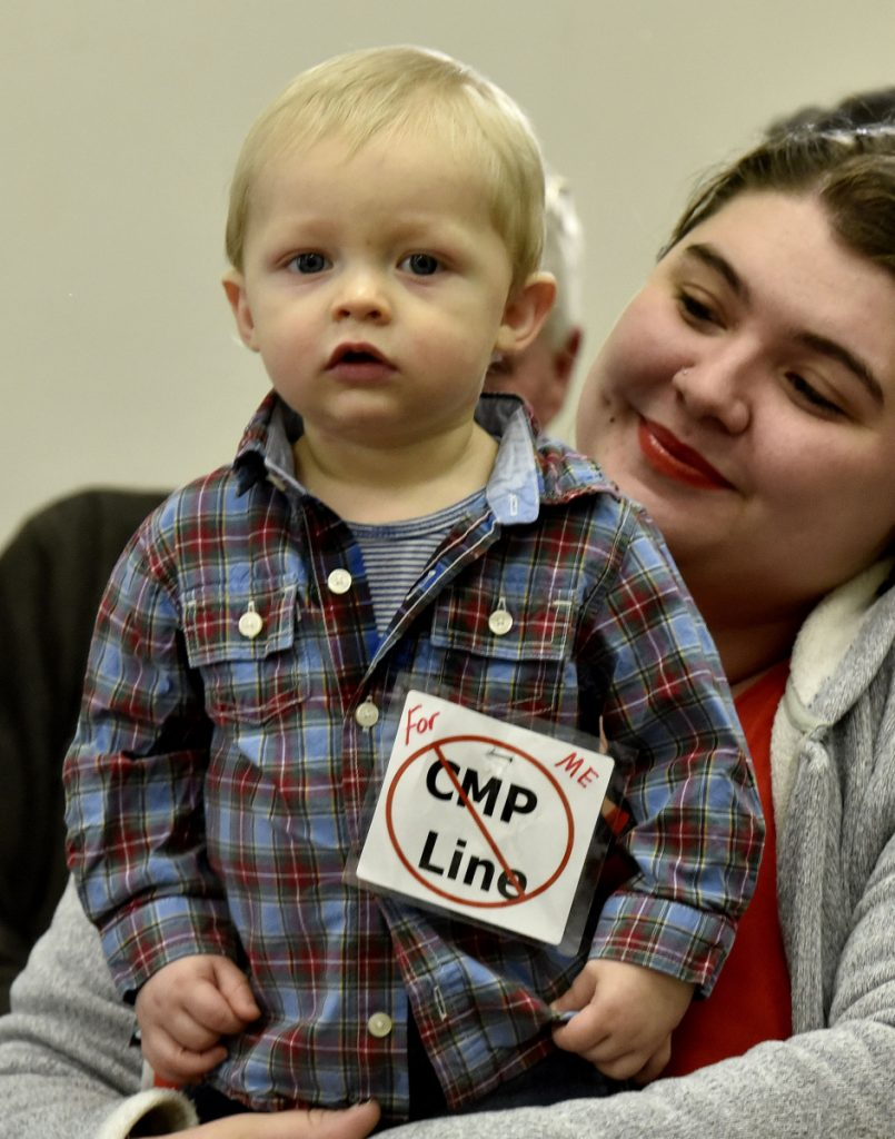 Mysadie Ayotte holds her son Xander, who wore a sign protesting CMP's New England Clean Energy Connect project prior to a meeting with Somerset County Commissioners in Skowhegan on Wednesday.