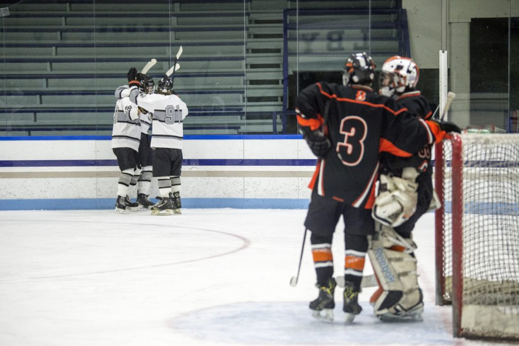 The Kennebec RiverHawks celebrate a goal, left, as Brewer's Aubrey Badger (3) talks to goalie Tyler St. Lawrence in the second period Wednesday at Colby College in Waterville.