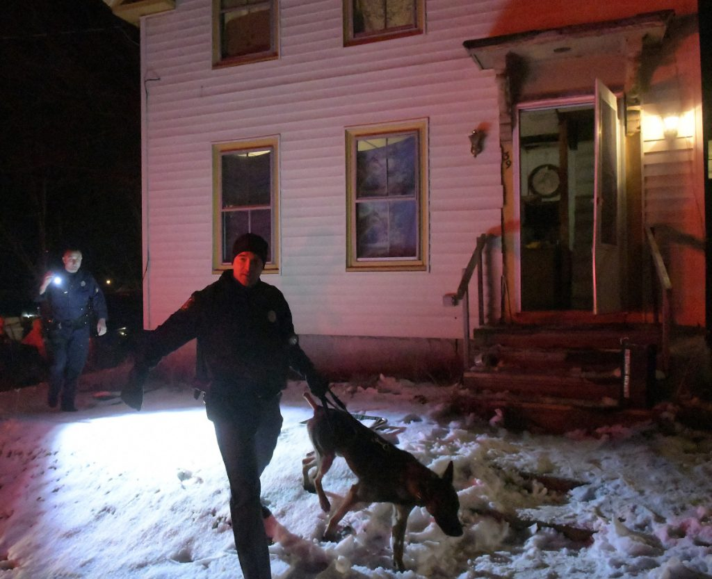 Cpl. Derek Record, left, and Trooper G.J. Neagle, both of the Maine State Police, use dogs to search a home at 39 Patterson St. in Augusta for suspects and drugs.