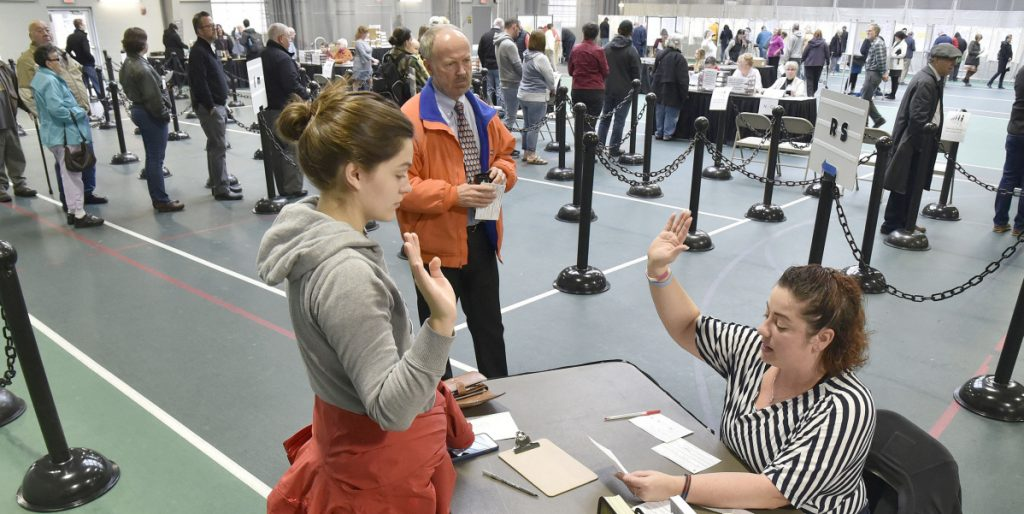 Colby College student Alexandria Fraize, left, swears on Nov. 6 the information she gave election clerk Allison Brochu is accurate before voting at Thomas College. City Solicitor Bill Lee observes.