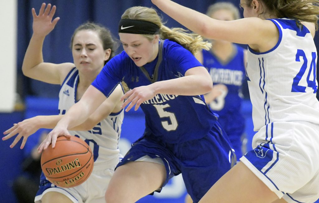 Erskine's Jordan Linscott, left, and Alyssa Savage try to trap Lawrence's Brooklyn Lambert during a Kennebec Valley Athletic Conference game Friday in South China.