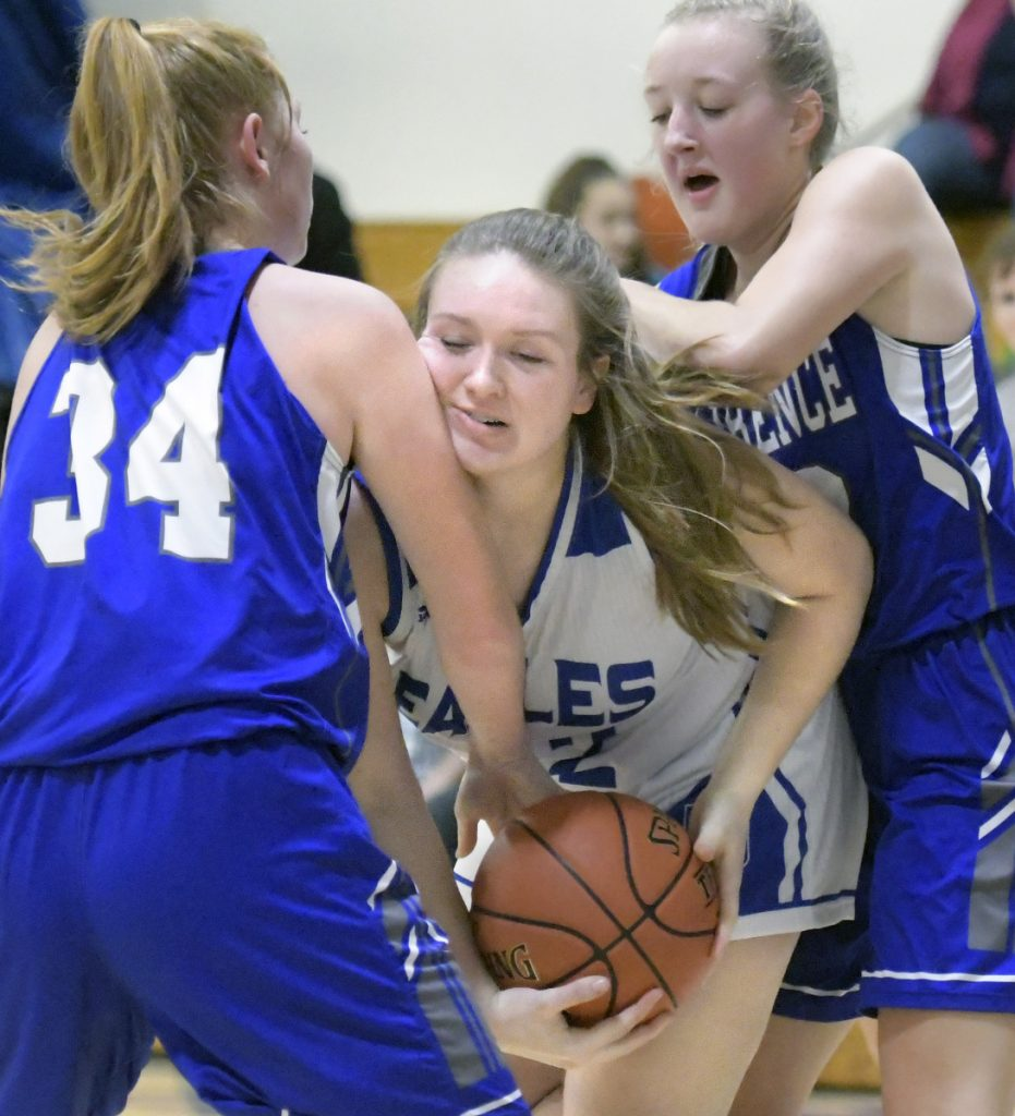 Erskine's Emily Clark, center, gets sandwiched by Lawrence's Sarah Poli, left, and Keagan Alley during a Kennebec Valley Athletic Conference game Friday in South China.