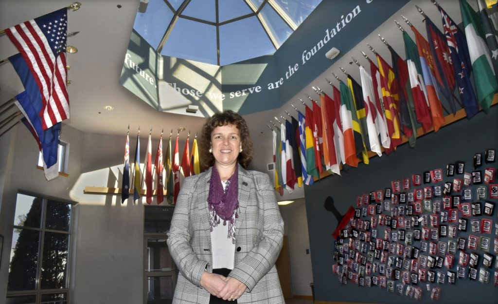 Thomas College President Laurie Lachance stands recently in the Hall of Flags lobby, where the flags of the countries of students attending the Waterville college are displayed. The college is working to grow the number of students attending the school from 772 to 1,000.