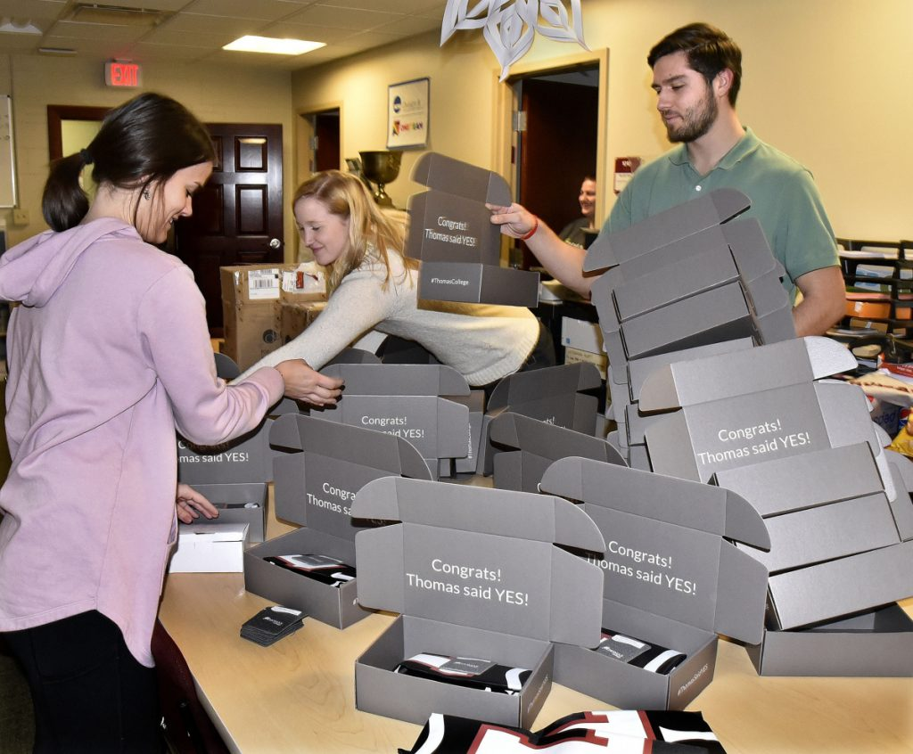 Thomas College staff members — from left, Cassidy Pinkham, Abby Dooley and Alan Wood — create gift packages Wednesday that will be sent to new students recently accepted to the Waterville college.