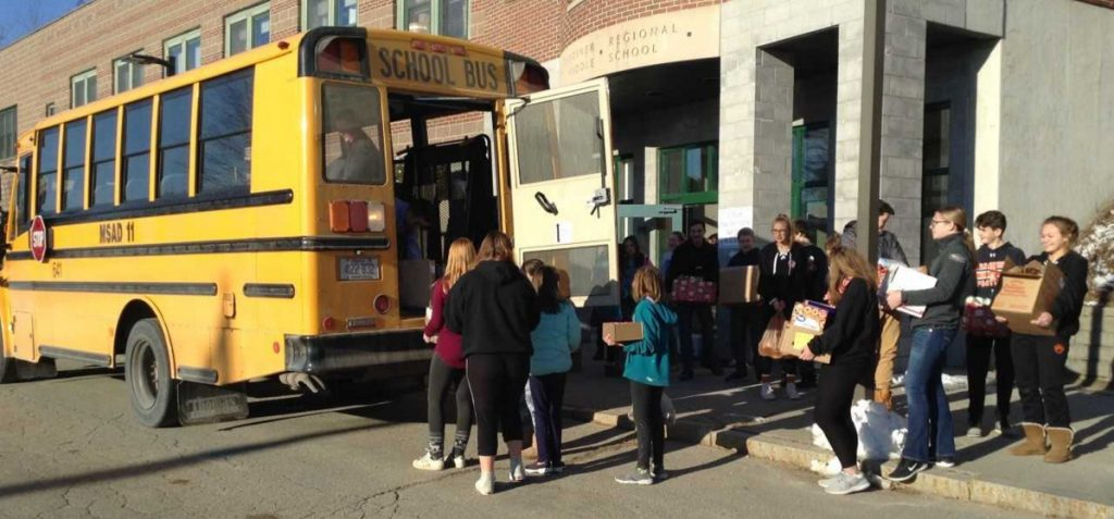 Gardiner Regional Middle School students and staff load a school bus full of food  items for the Chrysalis Place Food Pantry in Gardiner.